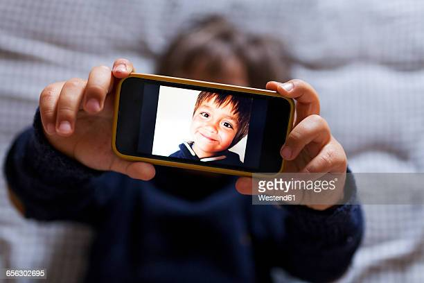 Little boy holding a cell phone with picture of himself