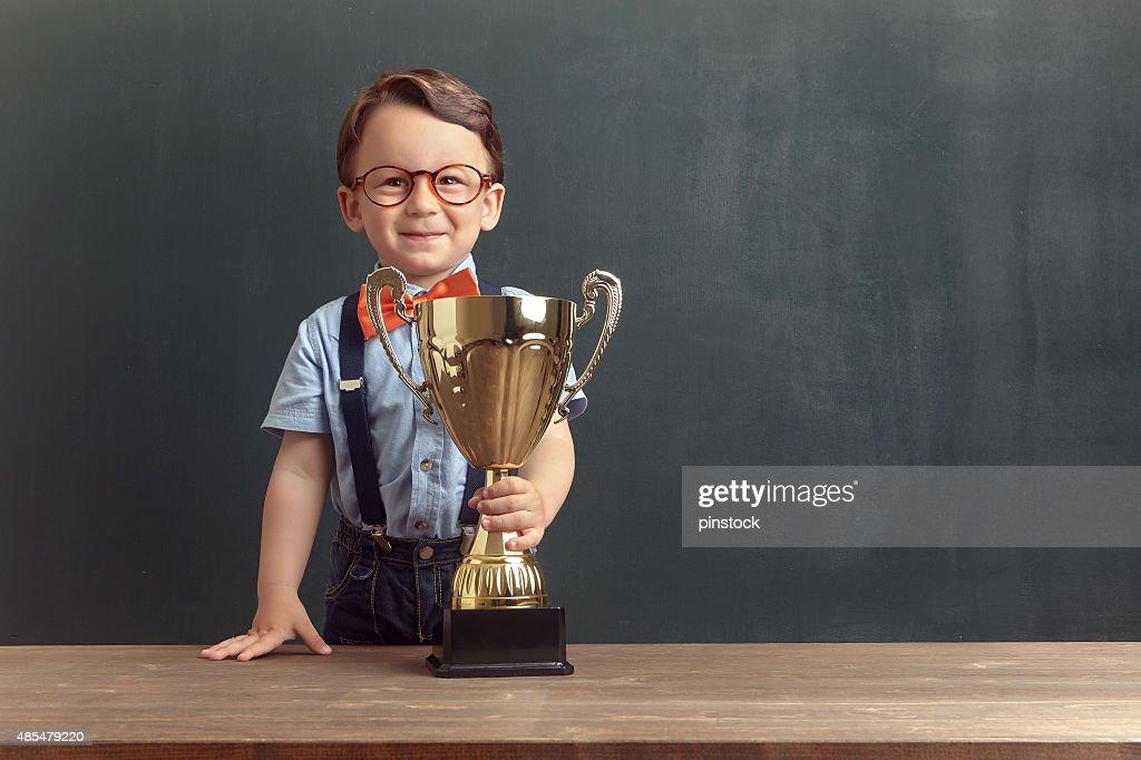 Little boy holding a golden trophy : Stock Photo