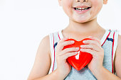 Little boy holding a red heart