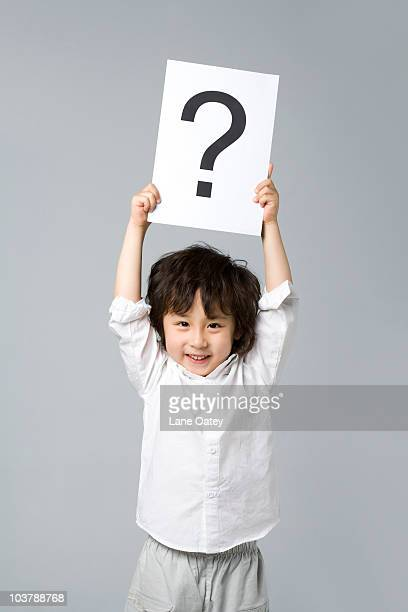 little boy holding a sign with a question mark - holding aloft stock pictures, royalty-free photos & images