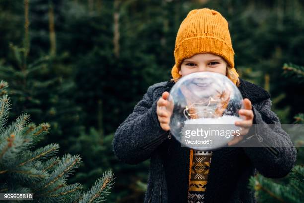 Little boy holding a snow-filled crystal ball, making a wish