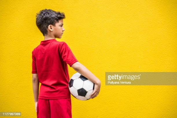 little boy holding a soccer ball - football strip stock pictures, royalty-free photos & images