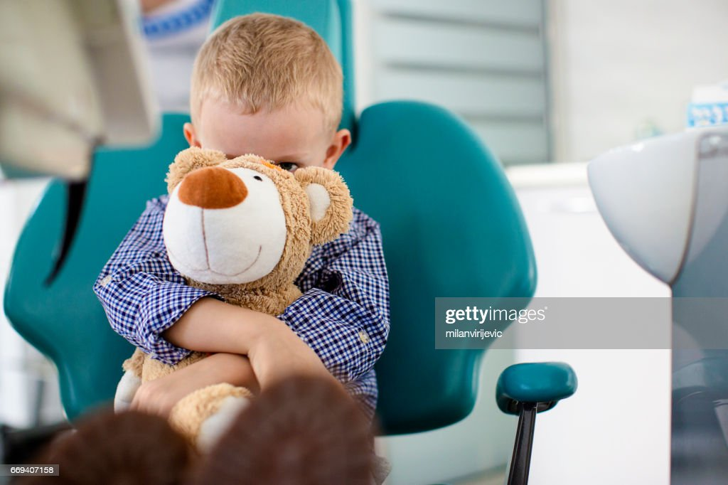 Little boy holding a teddy bear in his arms at dentists office : Stock Photo