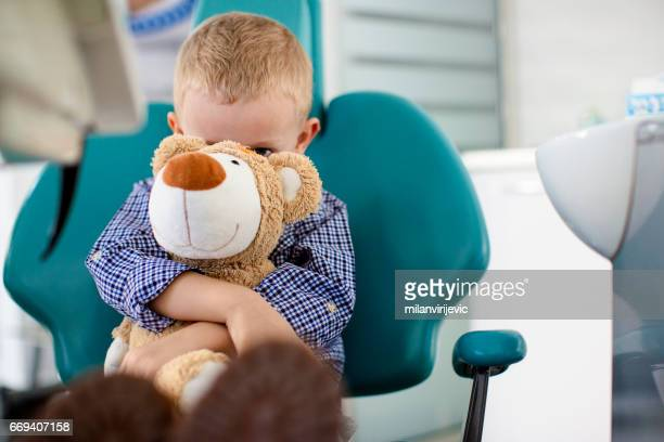 little boy holding a teddy bear in his arms at dentists office - bad teeth stock photos and pictures