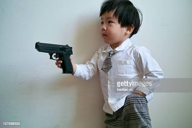 A little boy holding a toy gun.