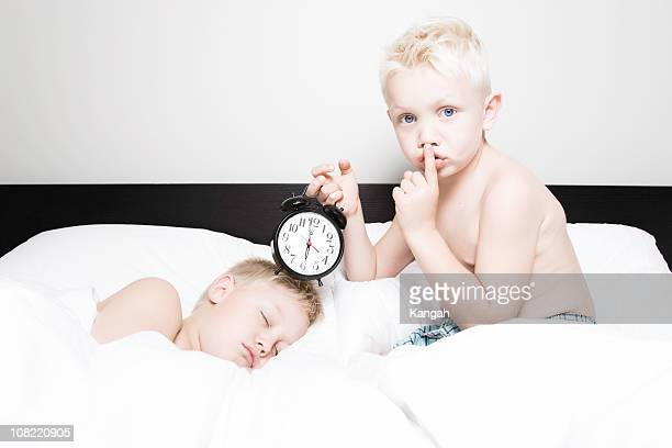 Little Boy Holding Alarm Clock to Sleeping Brother