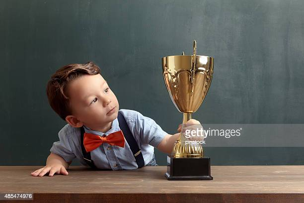 Little boy holding and looking towards a golden trophy