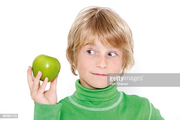 Boy (10-11) holding apple, close-up