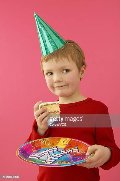 little boy holding birthday cake slice - gorro de fiesta fotografías e imágenes de stock