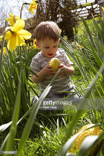 little boy holding Easter egg amongst daffodils