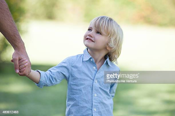 Little boy holding father's hand