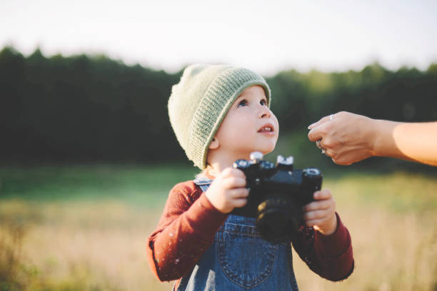 Little boy  holding film camera  in a large field in the country