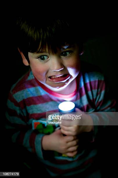 Little Boy Holding Flashlight Up to Face, Low Key