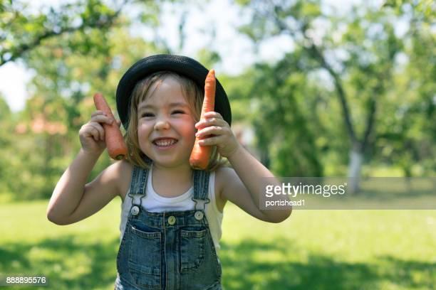 Kleiner Junge hält frische Bio-Karotten