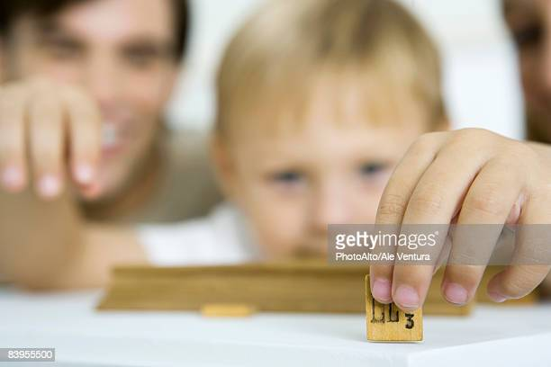 Little boy holding game piece, focus on foreground