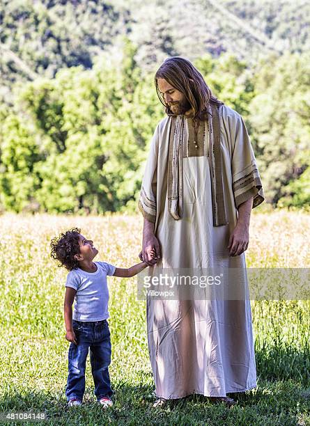 little boy holding hands with jesus christ - smiling jesus stock pictures, royalty-free photos & images
