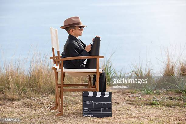 Little Boy Holding Megaphone And Sitting On Director's Chair
