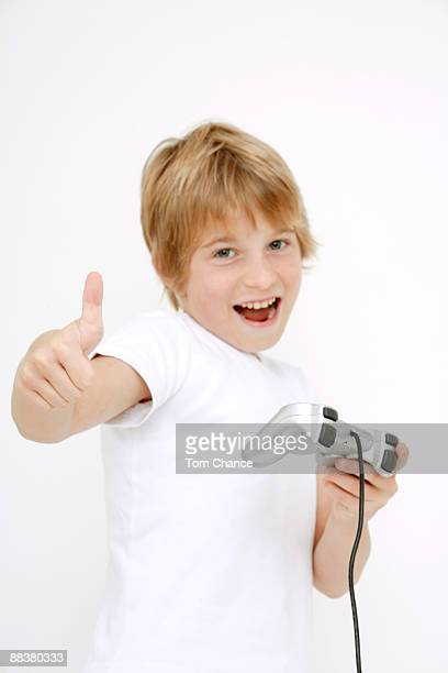 Boy (10-11) holding game console showing thumbs up, portrait, close-up