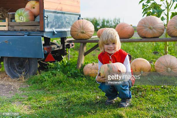 Little boy holding pumpkin
