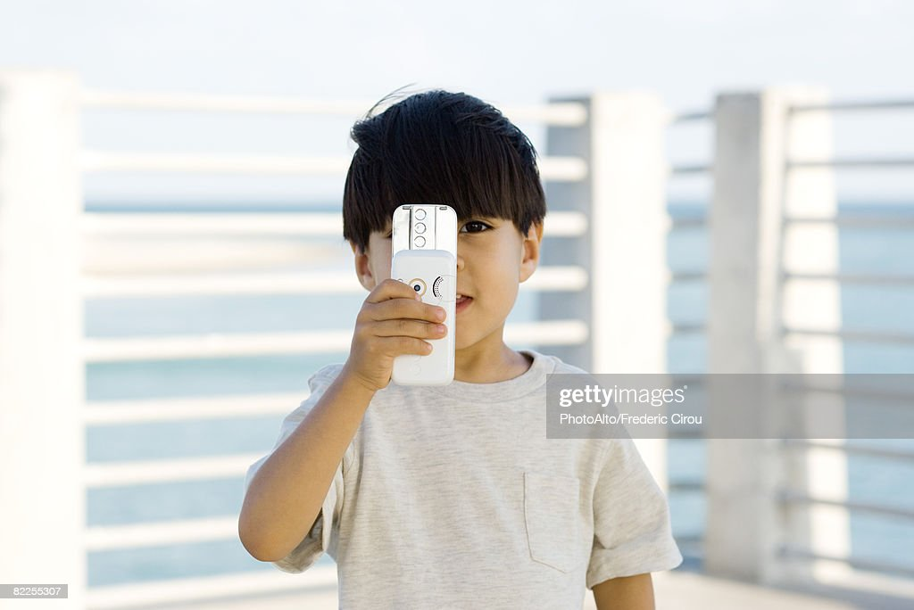 Little boy holding slide camera phone in front of face, looking at camera : Stock Photo