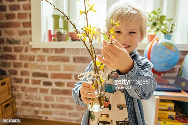 Little boy holding vase with willow catkin and forsythia