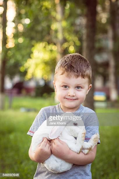 Little boy holding white Easter bunny