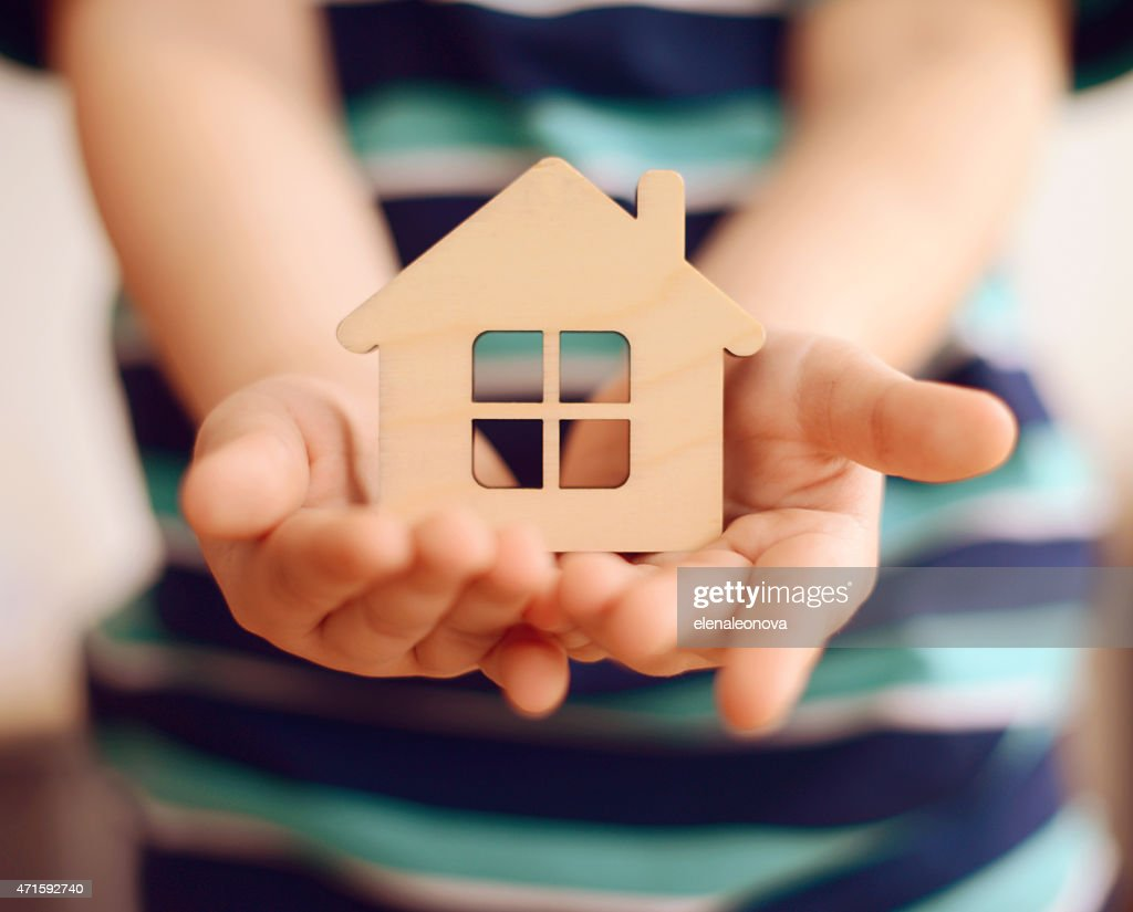 little boy holds in hands small toy house : Stock Photo