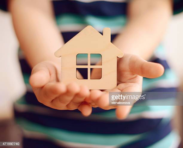 little boy holds in hands small toy house - home insurance stock pictures, royalty-free photos & images