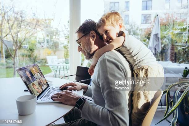 little boy hugging father from behind, while working from home - 在宅勤務 ストックフォトと画像