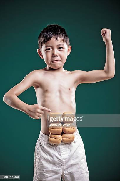 little boy imagines he has got strong muscle.