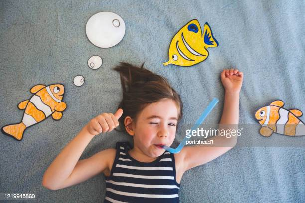 little boy imagines he is swimming in the ocean. covid-19 crisis - sailor suit stock pictures, royalty-free photos & images