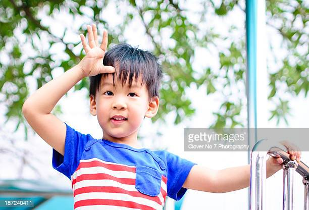 Little boy imitating soldiers who salute