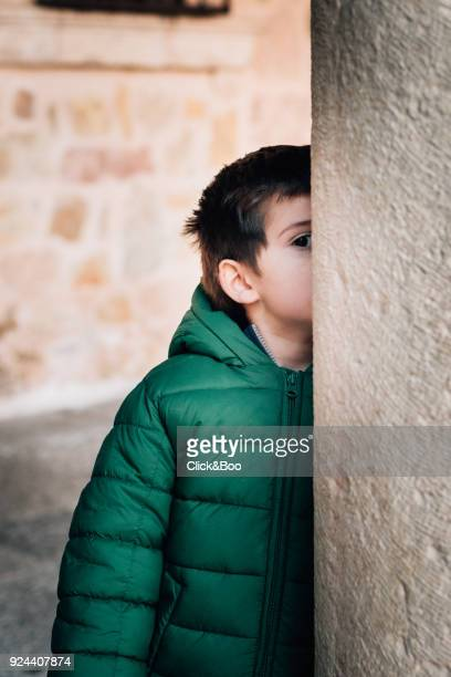 Little boy in a coat looking ata camera