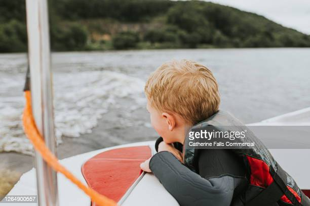 little boy in a lifejacket looking over the side pf a speedboat - sailing stock pictures, royalty-free photos & images