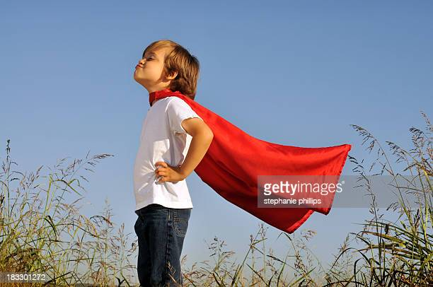 A little boy in a red superhero cape playing outside