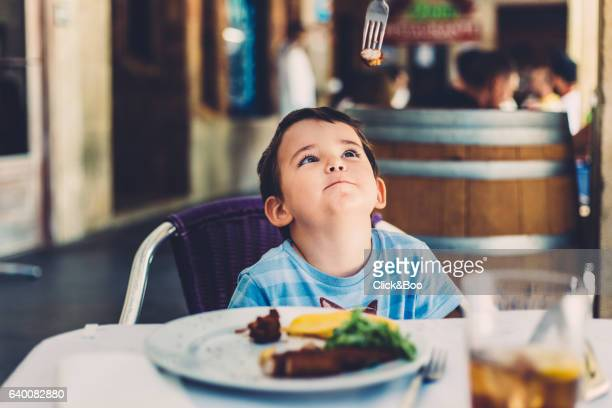 Little boy in a restaurant playing with a fork
