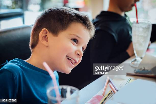 Little boy in a restaurant smiling looking away from camera