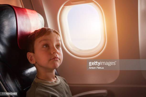 little boy in airplane seat sit by window - kid in airport stock pictures, royalty-free photos & images