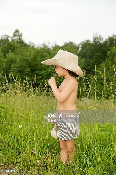 Little boy in big hat standing in a meadow