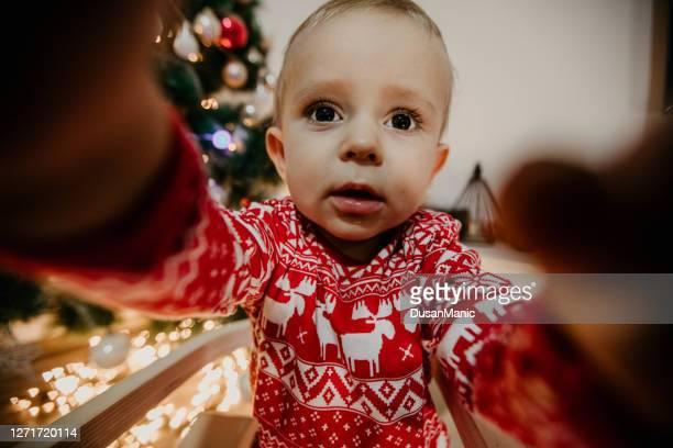 niño en pijama de navidad se sienta cerca de un árbol de navidad - new jersey fotografías e imágenes de stock