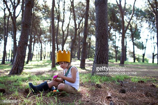 LIttle Boy in crown with Easter eggs in forest