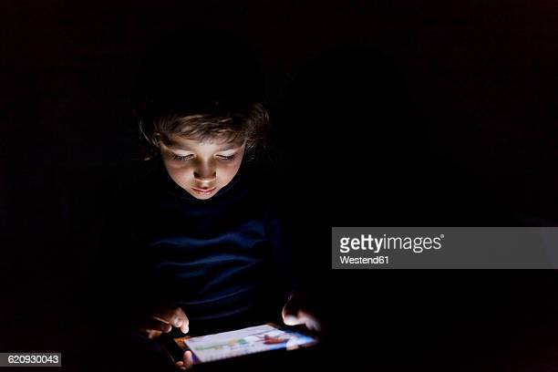 Little boy in darkness playing with digital tablet