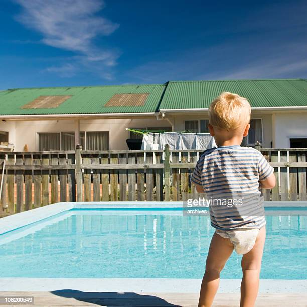 Little Boy in Diaper Looking at Backyard Pool