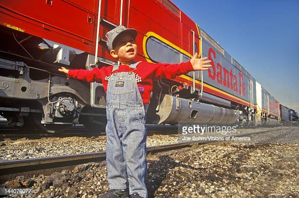 Little boy in engineers overalls and cap in front of train station Santa Fe Line Los Angeles CA