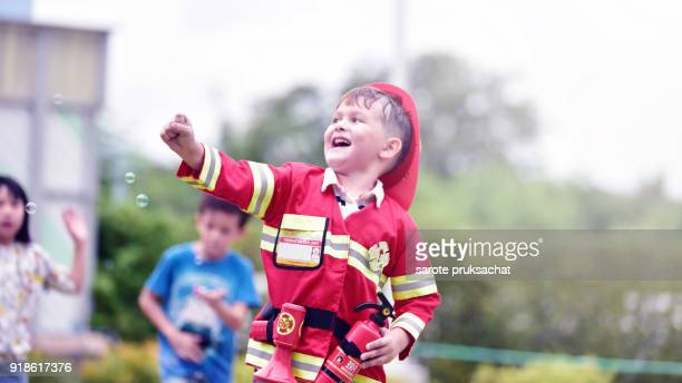 Little boy in fireman costume having fun on  a playground outdoors in summer. learning  in an international school .