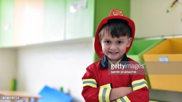 Little boy in fireman costume having fun on learning  in an international school .
