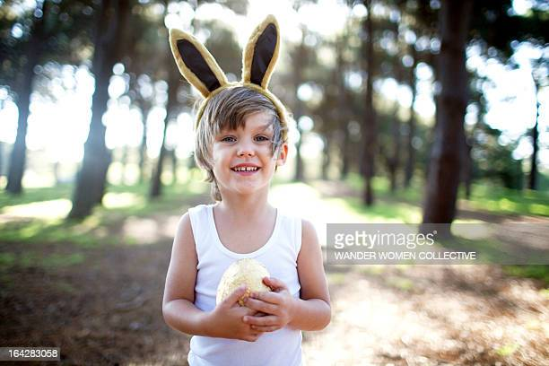 Little boy in forest holding golden Easter egg