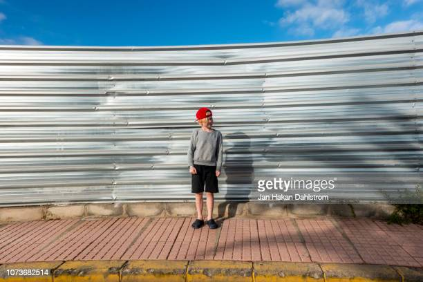little boy in front of steel barrier - construction barrier stock pictures, royalty-free photos & images