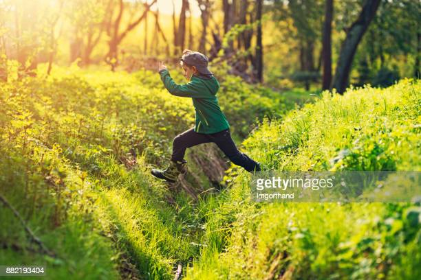 Little boy in galoshes jumping over a stream in forest