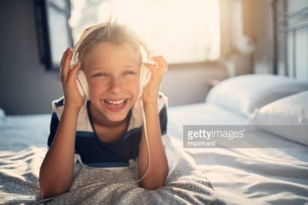 kleiner junge im kopfhörer musik hören - 8 9 jahre stock-fotos und bilder